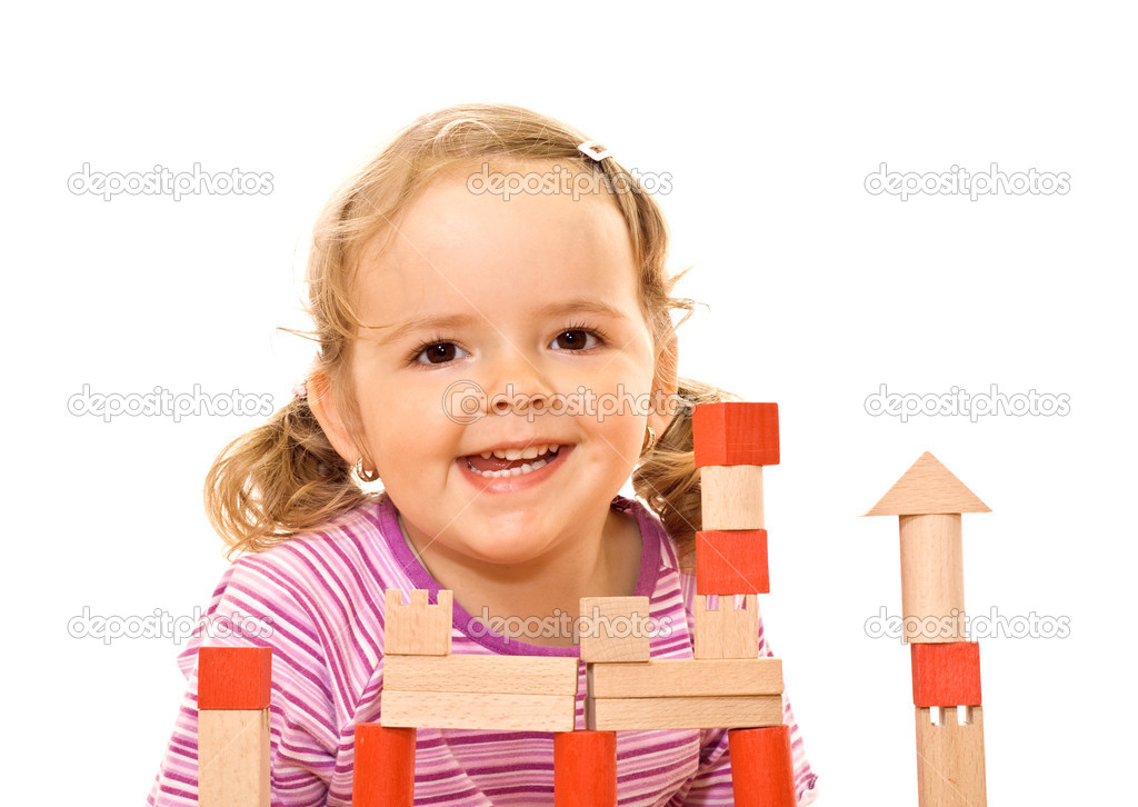 Happy girl posing behind a wooden blocks tower — Stock Photo #6409559