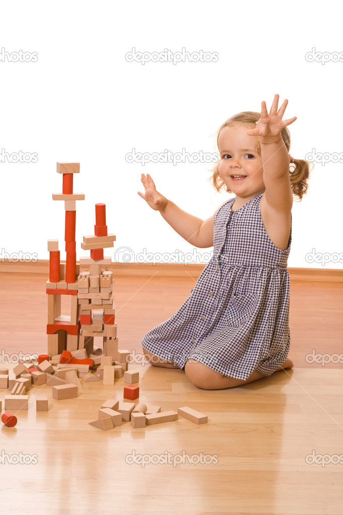Happy little girl playing with wooden blocks on the floor - isolated — Stock Photo #6409560