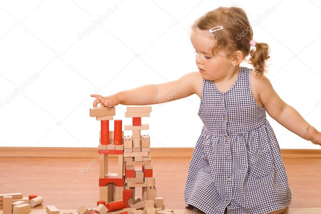 Cute little girl playing with wooden blocks  Stock Photo #6409561