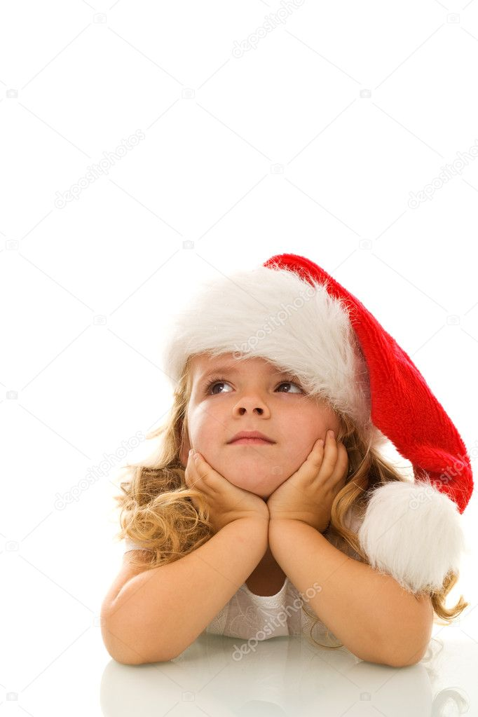 Little girl thinking about christmas, propping her head wearing santa hat  Stock Photo #6409713