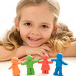 Little girl smiling with her clay family — Stock Photo