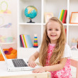 Little girl in her room working on laptop computer — Stock Photo #6410025