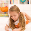 Royalty-Free Stock Photo: Little girl listening to music laying on the floor