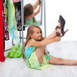 Little girl trying her mother's shoes and clothes — Stock Photo