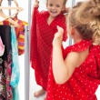 Happy little girl trying on dresses in front of mirror — Stock Photo