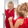 Little girl trying dress in front of mirror — Stock Photo #6410097