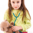 Adorable little girl playing doctor with a teddy bear — Stok fotoğraf