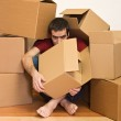 Man under cardboard boxes on the floor - moving concept — Stock Photo #6410237