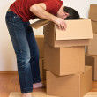 Man unpacking from cardboard boxes in a new home — Stock Photo #6410240