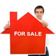 Confident salesman with house for sale sign — Stock Photo