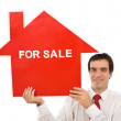 Salesman with house for sale sign — Stock Photo