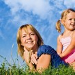 Stock Photo: Woman and little girl in the grass