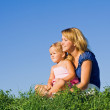 Woman and little girl outdoors sitting — Stock Photo #6410634