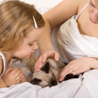 Stock Photo: Little girl and her mother stroking a kitten