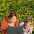 Stock Photo: Woman and little girl on the spring flower field