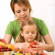 Woman and little girl slicing fruits — Stock Photo