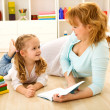 Story time - little girl and woman reading a book — Stock Photo
