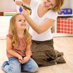 Woman combing little girls hair — Stock Photo #6410895