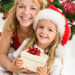 Merry christmas - woman and little girl with a present — Stock Photo