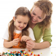 Woman and little girl playing with beads and a string — Stock Photo #6410954