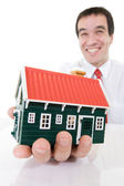 Ecstatic businessman with a miniature house — Stock Photo
