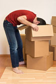 Man unpacking from cardboard boxes in a new home — Stock Photo