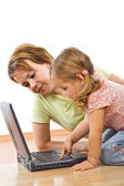 Woman and little girl with laptop — Stock Photo