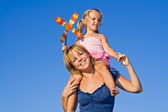 Woman with little girl against summer sky — Stock Photo
