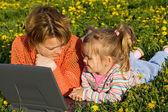 женщина и девочка расслабляющий на поле цветка — Стоковое фото