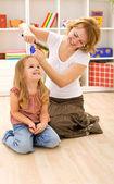 Woman combing little girls hair — Stock Photo