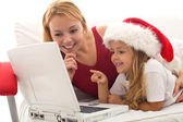 Woman and little girl playing on a laptop at christmas time — Stock Photo