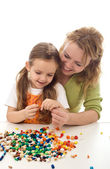 Woman and little girl playing with beads and a string — Stock Photo