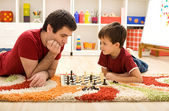 Man teaching boy the rules of chess — Stock Photo