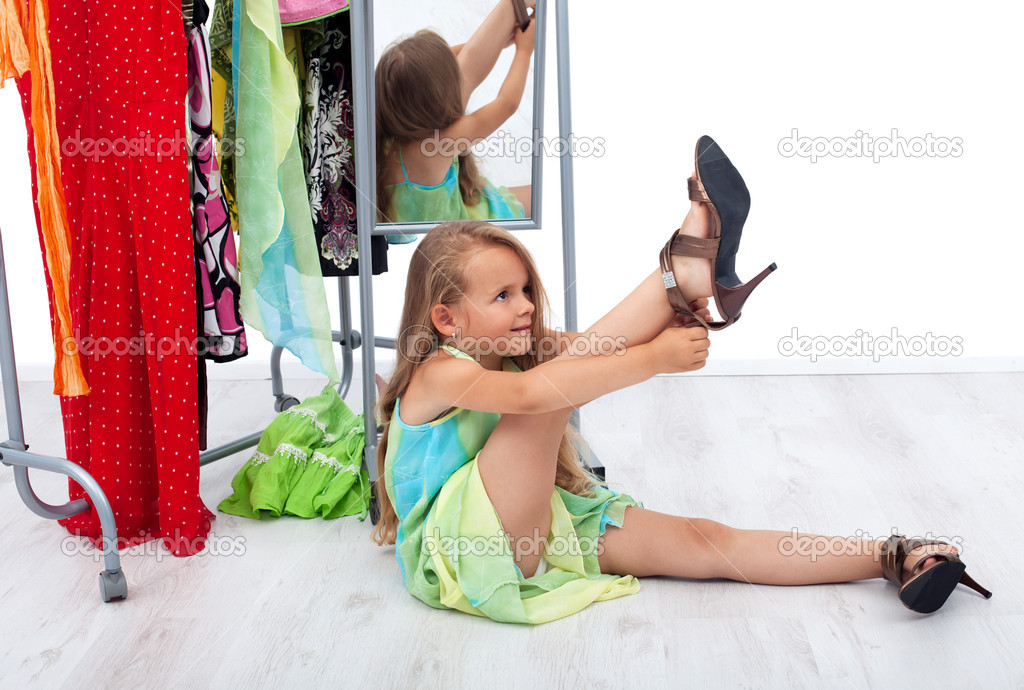 Little girl having fun trying her mother's shoes and clothes — Stock Photo #6410043