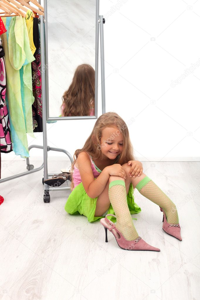 Little girl  sitting on the floor trying on high heel shoes — Stock Photo #6410074