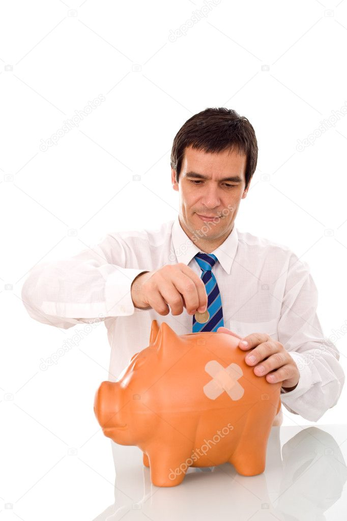 Businessman putting money in his wounded piggy bank - isolated  Stock Photo #6410242