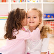 Little girls sharing a delightful secret - Stock Photo