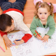 Two kids coloring on the floor - Stock Photo