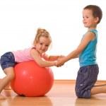 Little boy teaching her sister gymnastics — Stock Photo #6430077