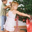 Kids decorating the christmas tree — Stockfoto