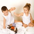 Kids playing with their kitten on the bed — Stock Photo #6430158