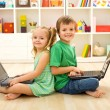 Happy kids with laptops sitting on the floor — Stock Photo