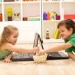 Kids with laptops eating popcorn — Stock Photo #6430237
