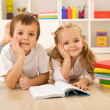 Happy kids with books laying on the floor — Stock Photo #6430239