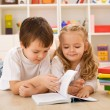 School boy teaching and showing her sister how to read — Stock Photo #6430240