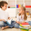 Stock Photo: School boy showing her little sister how to read