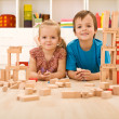 Happy kids with wooden blocks on the floor — Stock Photo #6430263