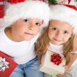 Christmas kids with santa hats and presents — Stock Photo
