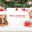 Kids laying under the christmas tree - Stock Photo