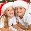 Happy kids in front of christmas tree — Stock Photo